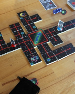 Galactic Travels is a portable boardgame that consists of a set of tiles and cards. In this two player game you must find 3 aliens to win. By connecting the tiles you can find different cards and maybe find one of the aliens. During the game you can attack the ship of your enemy and you must survive the different hazzards that will try to kill you. By using a level meter and dice you can defeat the hazzards. Wormholes will warp you to different spots on the map. Do you have the courage to find these 3 aliens?